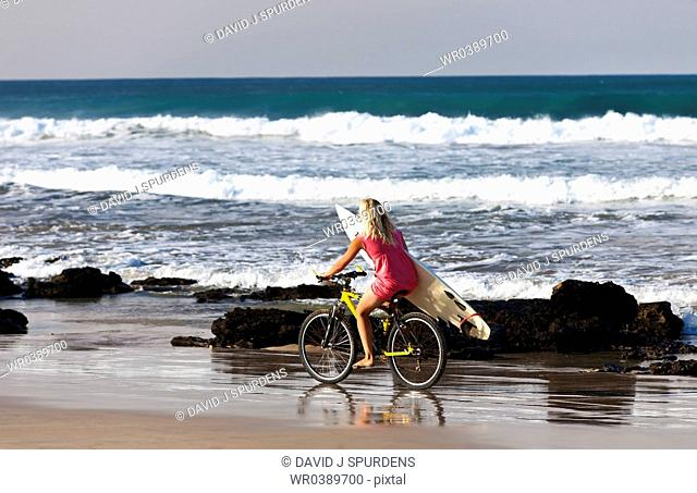 A surfer girl rides along beach to the waves