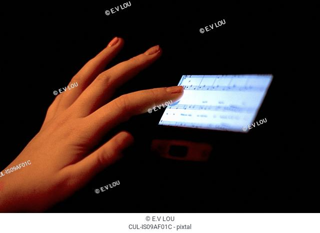Close up of hand using touchscreen displaying sheet music