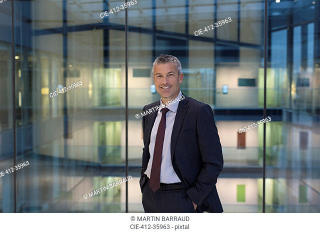 Portrait smiling, confident businessman in modern office atrium