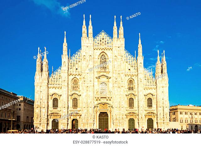Milan Cathedral (Duomo di Milano) is the gothic cathedral church of Milan, Italy. Shot in the dusk from the square ful of people
