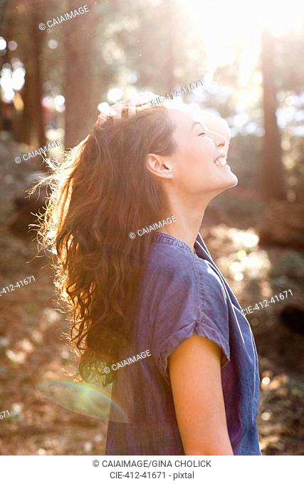 Smiling, carefree woman in sunny woods