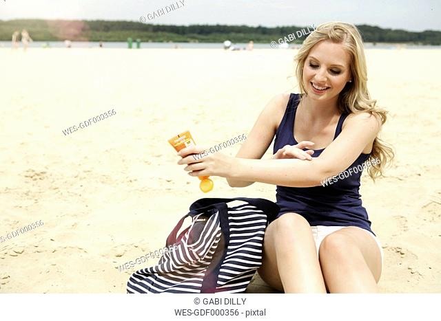 Smiling young woman sitting on the beach using suncream
