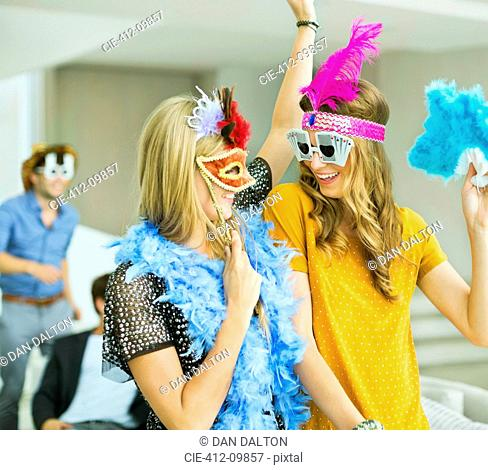 Women wearing decorative glasses and headpieces at party