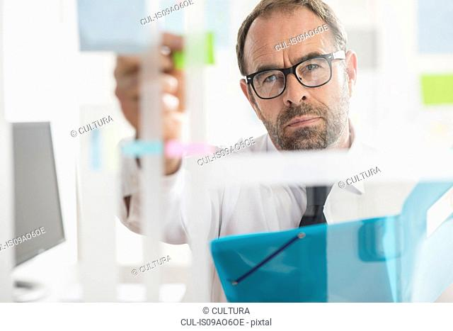 Businessman sticking adhesive notes to glass wall in office
