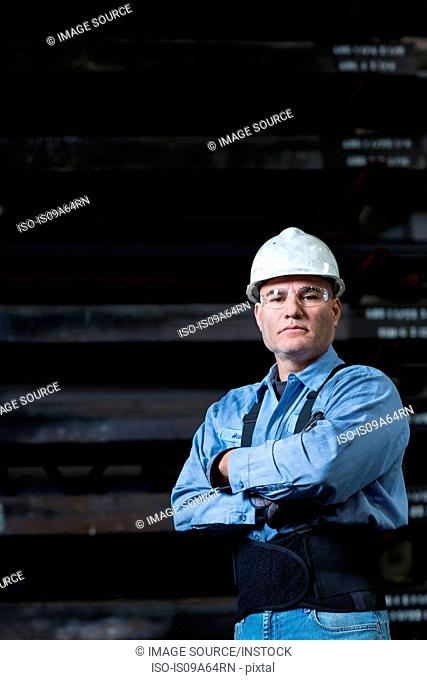 Worker in weight belt in metal plant