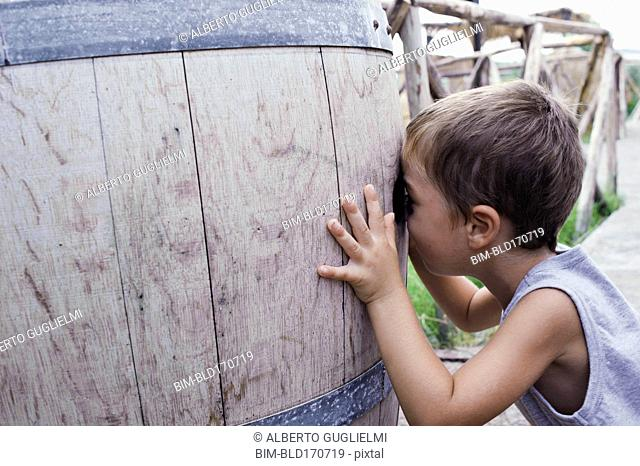 Caucasian boy peering into barrel