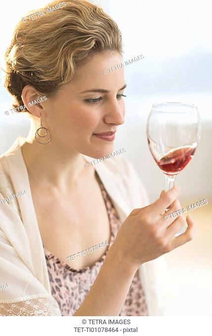 Young woman swirling glass of red wine