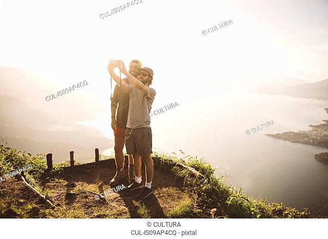 Two young men taking selfie at Lake Atitlan on digital camera, Guatemala