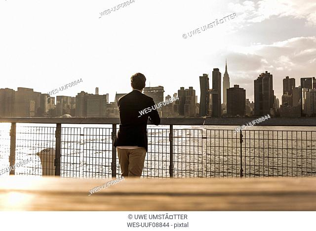 USA, New York City, back view of businessman looking at skyline of Manhattan