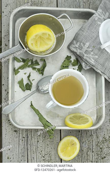 Hot lemon tea with dried lemon leaves on a metal tray