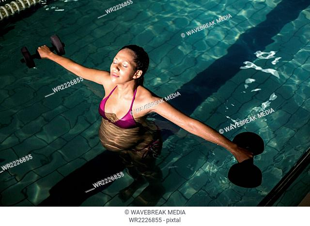 Pregnant woman exercising in the pool with weights