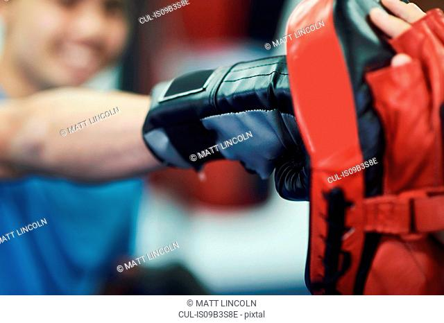 Hand of male boxer punching punch mitt, close up