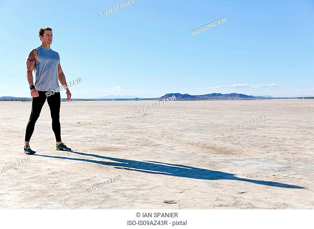 Man training, looking out from dry lake bed, El Mirage, California, USA