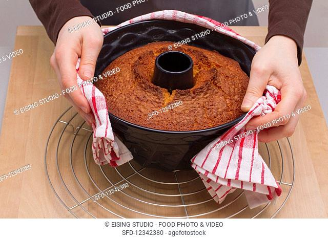 Removing a cake from a tin - wrap the tin in a damp tea towel and turn the cake out onto a cooling rack
