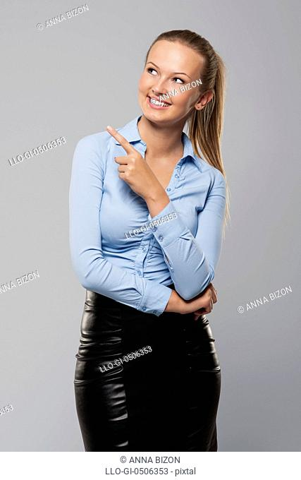Smiling businesswoman pointing at copy space, Debica, Poland