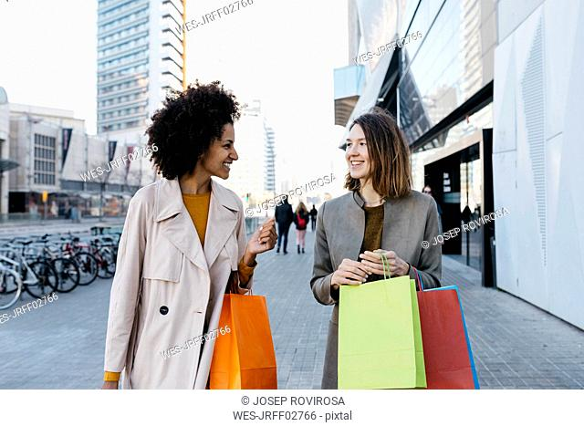 Two happy women with shopping bags walking in the city