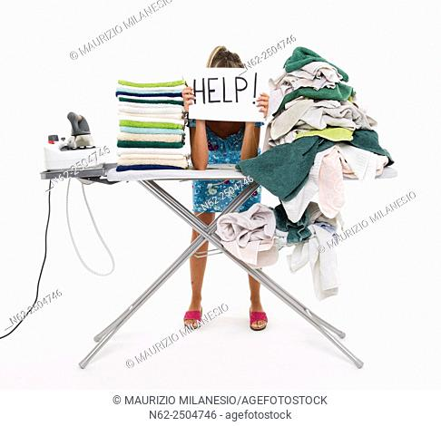 Woman behind a board covered with clothes to be ironed, exposes a sign reading aid