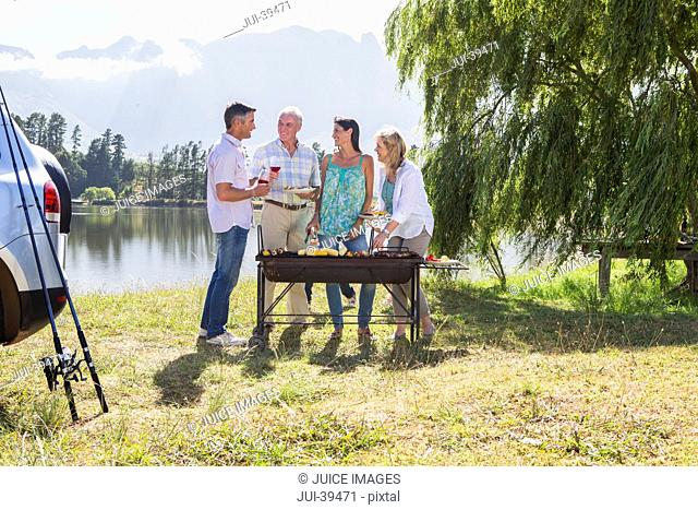 Adult Family Group Cooking Barbeque In Countryside