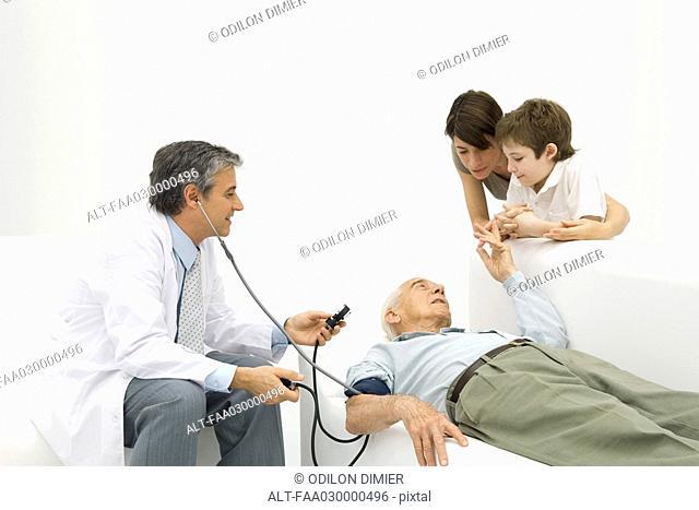 Doctor measuring elderly man's blood pressure, family watching