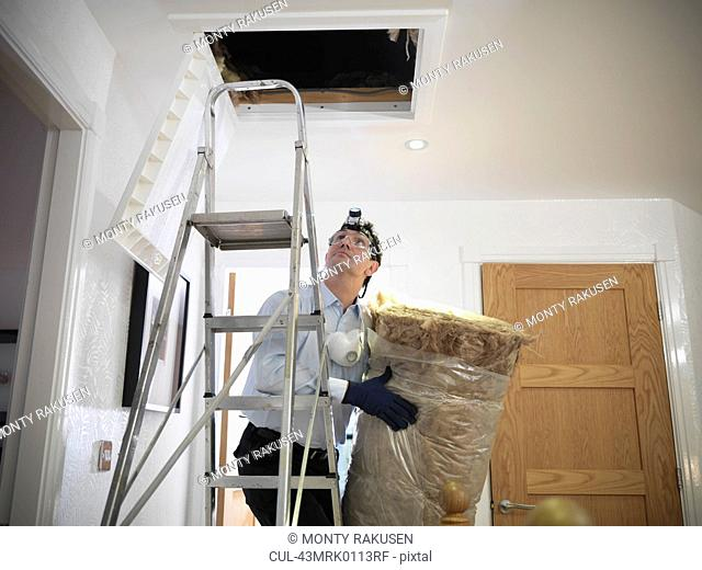 Worker carrying insulation to attic