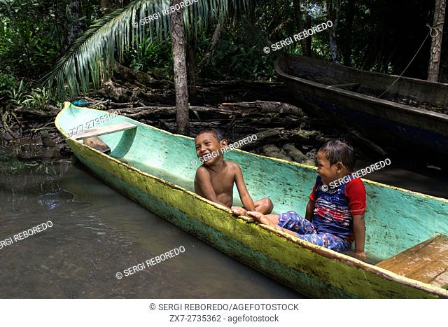 Kids play in one of the local boats used by the Ngobe Indians as their main form of transport, sheltered under a makeshift lean-to
