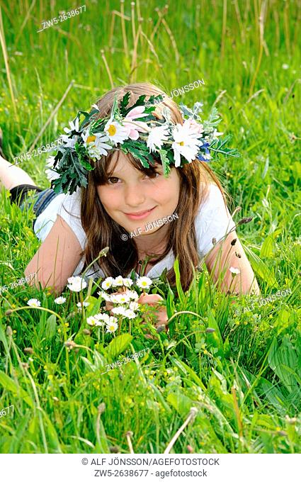 Girl, ten years old and with flowers in her hair lying in a grass