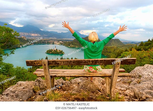 Relaxed female traveler, arms rised, enjoying beautiful panoramic view of Julian Alps, Lake Bled with St. Marys Church of the Assumption on the small island