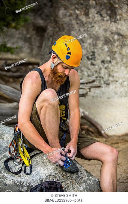 Caucasian rock climber tying shoe