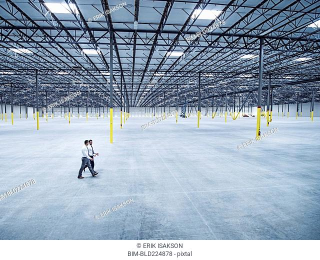 Businessmen walking in empty warehouse