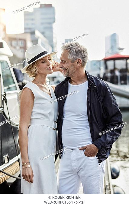 Older man and young woman at a marina next to a yacht