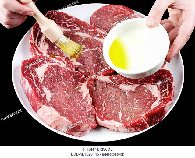 Brushing beef steaks with olive oil