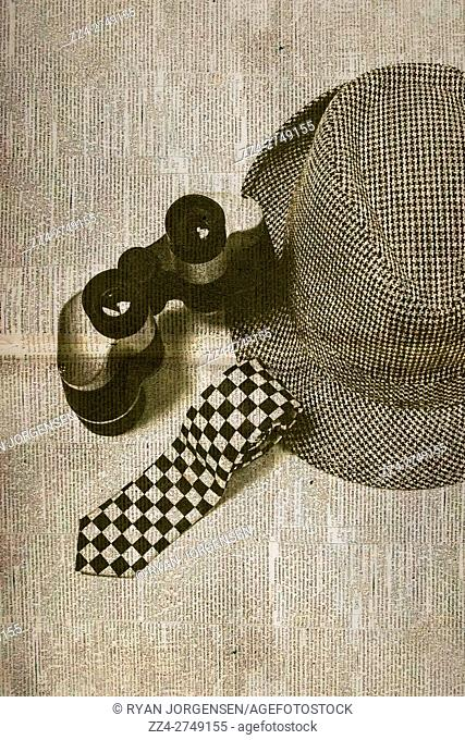 Vintage still life photo of a undercover tie binoculars and hat on reporting chronicles newspaper. Nostalgic journalism