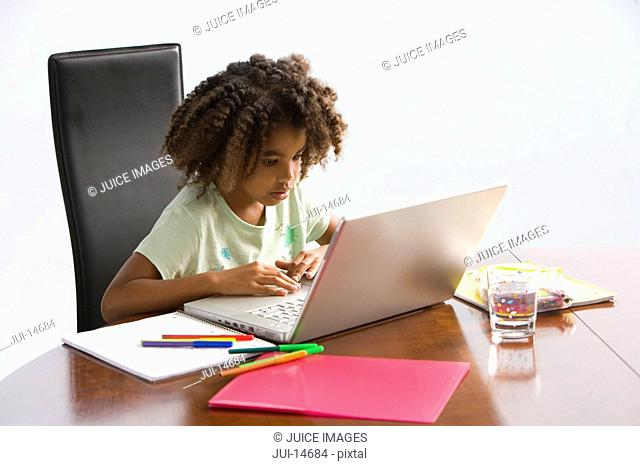 Girl 7-9 at laptop computer