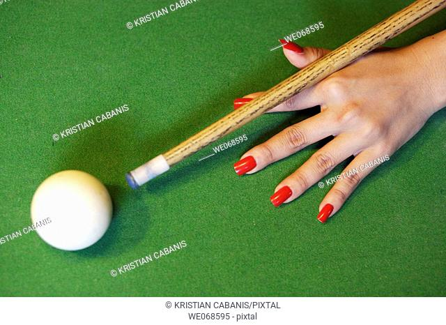Female hand with red nails holding the queue and targeting the white ball at a snooker game, Bangkok, Thailand, Southeast Asia