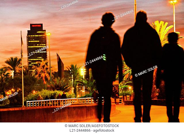 Mapfre tower at sunset. First, three black blurred silhouettes of people. Barcelona, Catalonia, Spain