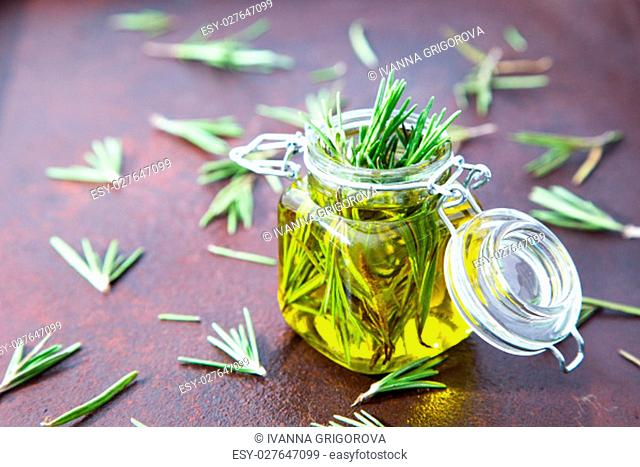Rosemary oil. Rosemary essential oil jar glass bottle and branches of plant rosemary with flowers on rustic background