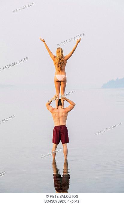 Young couple on beach, woman standing on man's shoulders, rear view