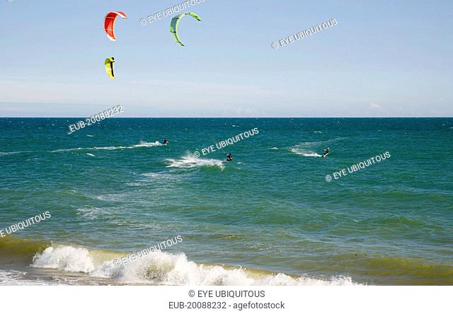 Kite Surfers on sea next to beach in the summer with blue sky