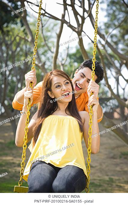 Man pushing a woman on a swing