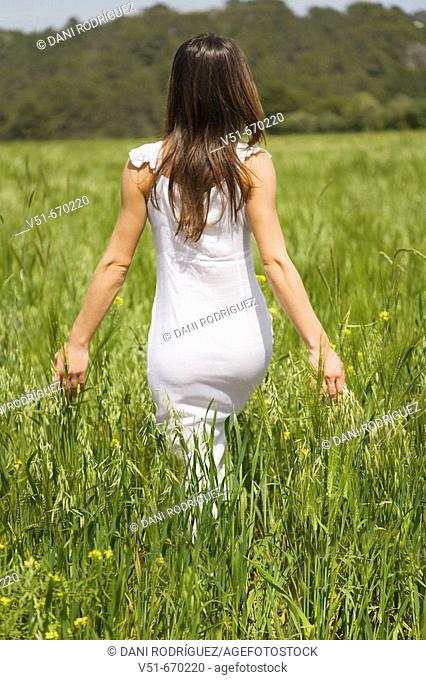 Woman in white dress walking in the countryside