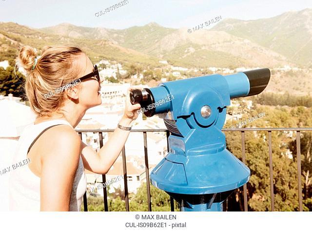 Woman by telescope on viewing platform, Mijas Pueblo, Andalucia, Spain