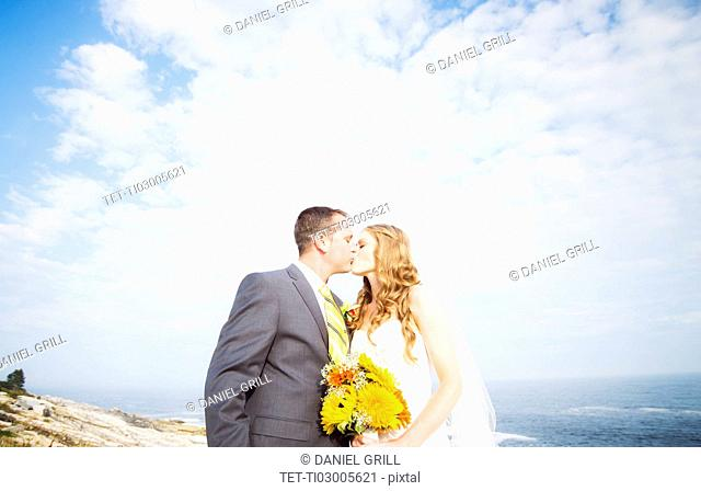 Portrait of married couple kissing