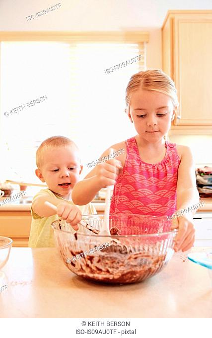 Siblings melting chocolate in mixing bowl