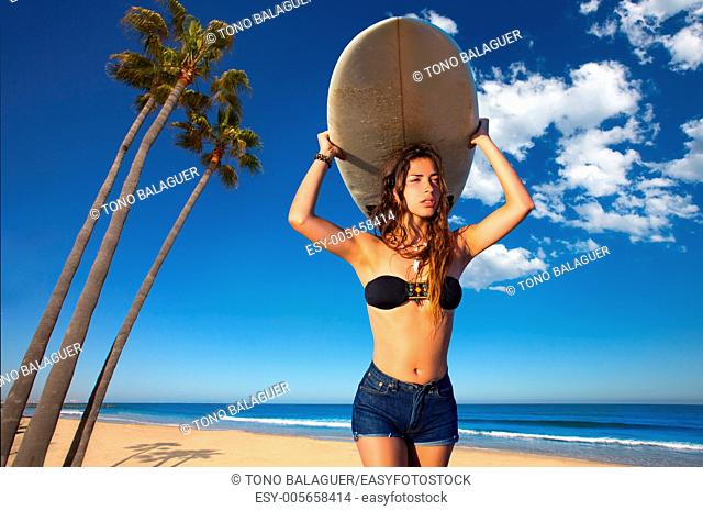 Brunette surfer teen girl holding surfboard in California palm trees beach