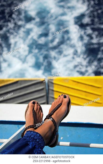Woman's feet on the seat of a deck ferry with the waves at the background, Milos, Cyclades Islands, Greek Islands, Greece, Europe