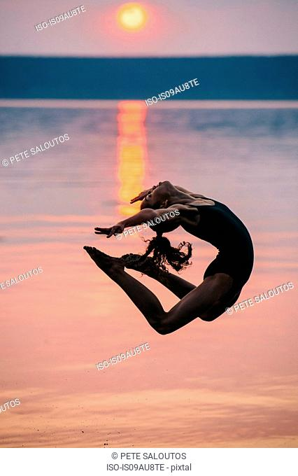 Side view of girl by ocean at sunset, leaping in mid air bending backwards