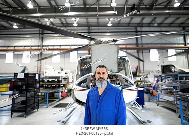 Portrait confident helicopter mechanic in airplane hangar