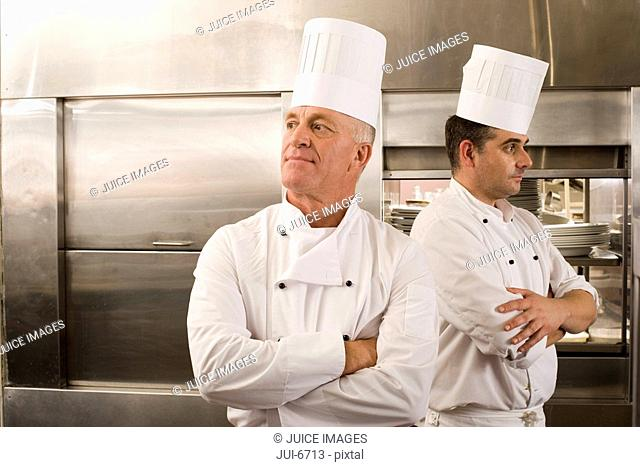 Two male chefs standing in commercial kitchen, arms folded, looking in opposite directions