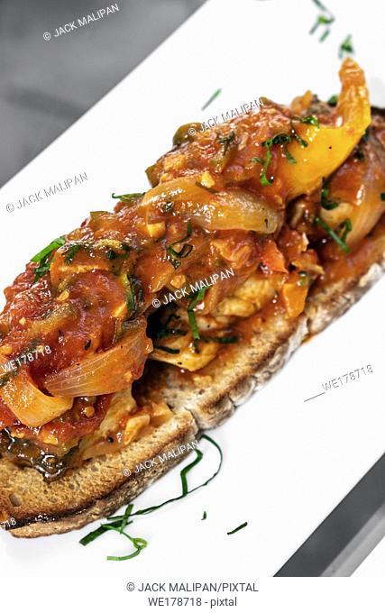 portuguese caldeirada de peixe spicy tomato onion and peppers fish stew on rustic tiborna toast tapas style