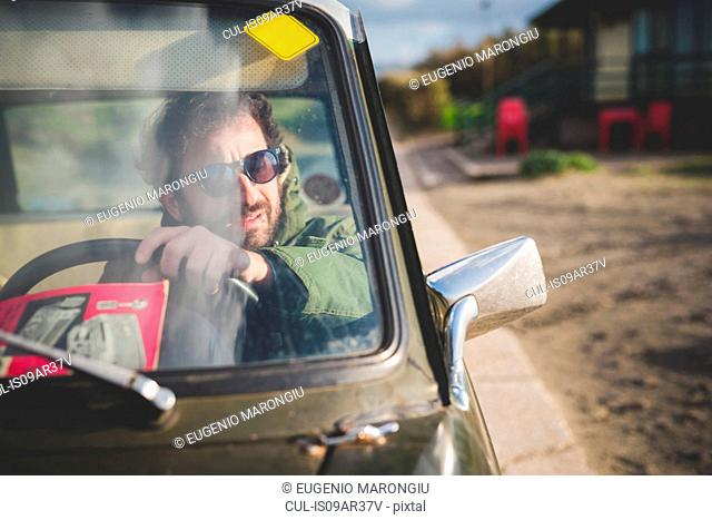 Man in parked vintage car looking through wing mirror
